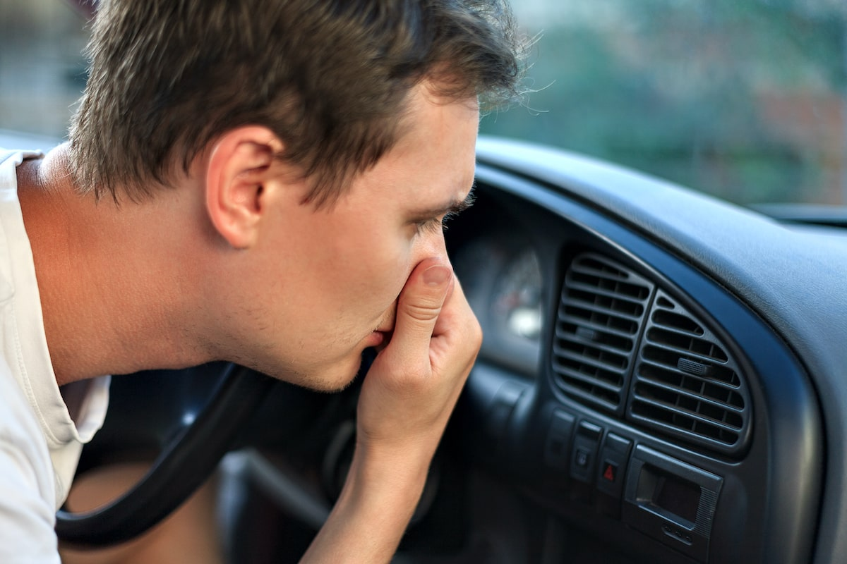 car making funny smell with man holding nose over ac