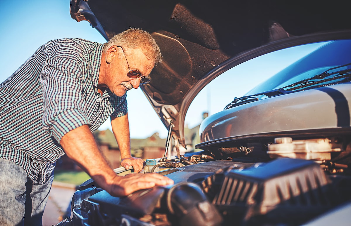 old man checking car engine for signs of damage