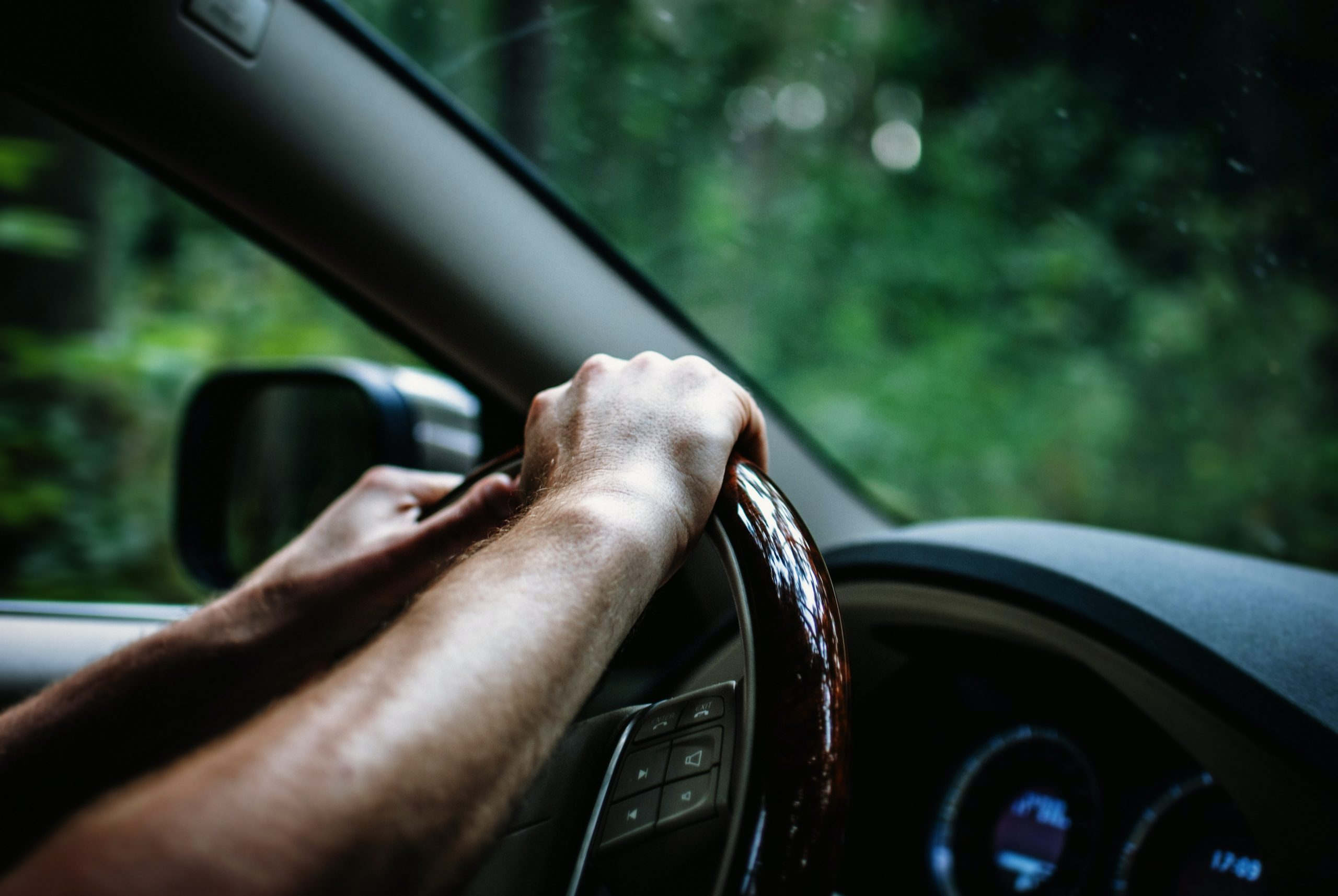 person having both hands on the steering wheel