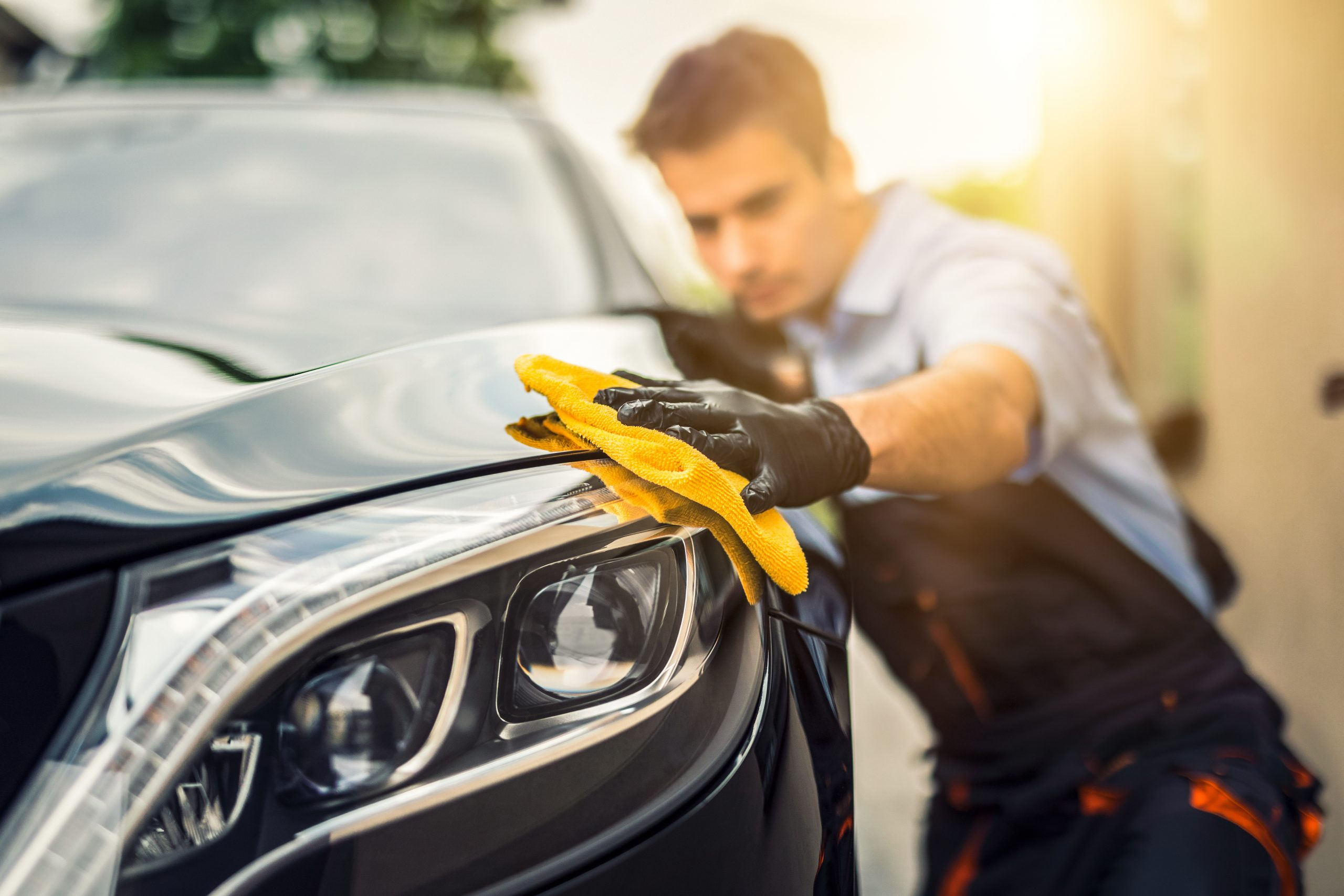 man using a yellow microfiber towel to polish and buff a black mercedes benz