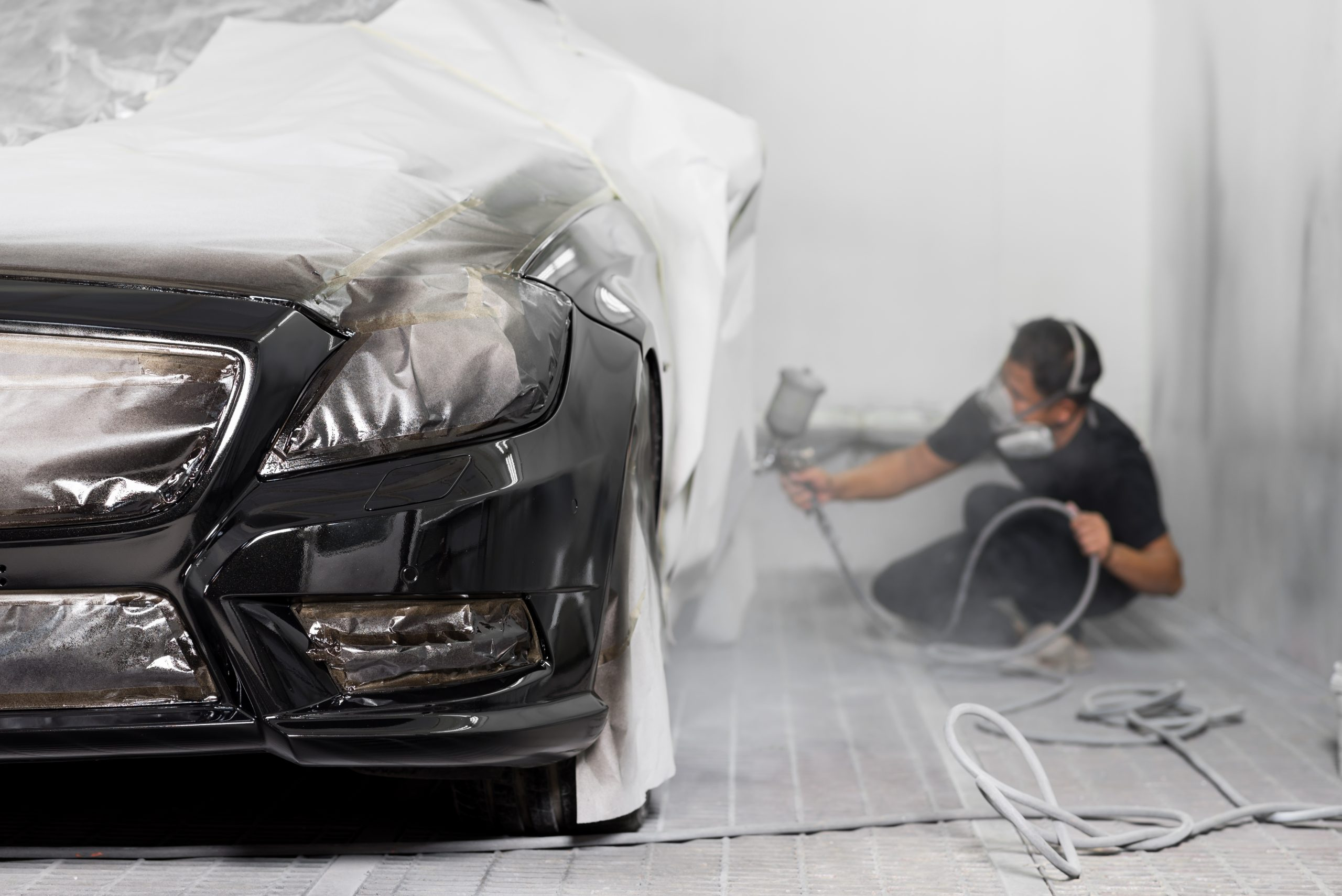 technician spraying paint on a black vehicle